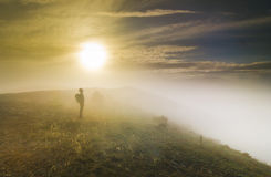 Man standing on a hill in foggy weather at sunset Royalty Free Stock Image