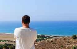 Man standing on a hill and looking over the sea Stock Photography