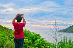 The man standing on the hill. And he use his moblie phone to take photo during sunset of ocean view Royalty Free Stock Images