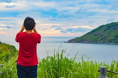 The man standing on the hill. And he use his moblie phone to take photo during sunset of ocean view Stock Photos