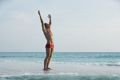Man standing with his arm outstretched on the beach. Man standing at the edge of the beach with his arm outstretched on the beach Royalty Free Stock Photos