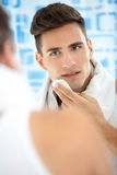 Man standing in his bathroom after shaving in the morning Stock Images