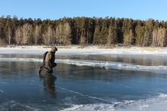Man  standing on his knee looking at the ice on a  a frozen river Royalty Free Stock Photos