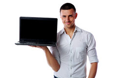 Man standing and holding laptop with blank screen Stock Images