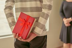 Man standing and holding red gift box behind his back.  Stock Photos