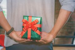 Man standing and holding valentine`s gift box behind his back. For surprise his lovely girlfriend Stock Images