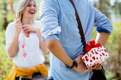 Man standing and holding white surprise gift box behind his back. As birthday present Stock Image
