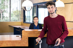 Man Standing At Hotel Reception stock photos
