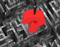 Man standing huge question mark in center maze old concrete. Man standing on top of huge 3D red question mark in center of maze with old mottled concrete texture Royalty Free Stock Photos