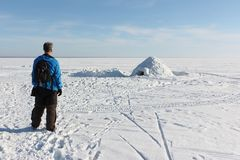 Man standing by an igloo on the frozen reservoir. In winter, Novosibirsk, Russia Royalty Free Stock Photo