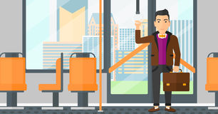 Man standing inside public transport. A man with a suitcase standing inside public transport vector flat design illustration. Horizontal layout Stock Photos