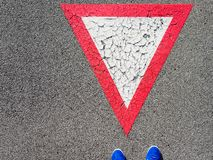 Man standing on inverted white with red border triangular road sign yield that you need to wait royalty free stock image