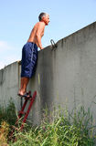 Man standing on a ladder. And looking over the fence Stock Photo