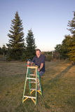 Man Standing With Ladder Stock Photo