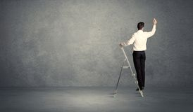 Businessman drawing on grunge wall. A man standing on ladder drawing with chalk in his hand on clear wall pattern background Royalty Free Stock Photography