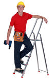 Man standing on ladder rung Stock Photo