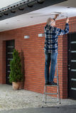 Man standing on the ladder and tightening ventilation grille. Vertical Royalty Free Stock Image