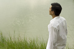 Man standing beside lake Stock Images