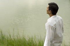 Man standing beside lake Stock Images