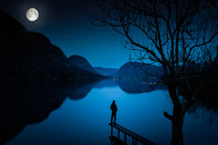 Man Standing by Lake, Covered with Moonlight Stock Photo