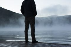 Man standing on lakefront on foggy day Royalty Free Stock Photography