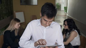 Man standing with laptop and his colleagues on background. In front of camera there is male in white shirt with dark tousled hair holding pearl tablet. While stock video footage