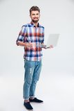 Man standing with laptop and showing thumb up sign Stock Photos