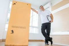 A man standing beside a large package royalty free stock photography