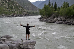 Man standing on a large rock spread his arms over mountain river.  Royalty Free Stock Photography