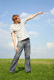 Man standing on lawn and pointing for finger Stock Images