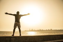 Man Standing on Ledge While Spreading Arms stock photo