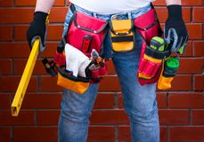 Man with standing level in his hand against the background of a red brick wall with a full tool bag. DIY.  stock photography