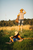 Man standing, looking away and searching her girlfriend. Brunette woman with long hair wearing dress hiding and lying on grass. Co Royalty Free Stock Photo