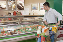 Man standing and looking at the Deli counter, trying to decide Stock Photos