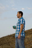 Man standing and looking out. Man standing and looking out onto a hillside holding a cup in his hand wearing a plaid shirt Royalty Free Stock Photography