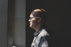 Man Standing Looking Straight Forward Through the Window Stock Photography