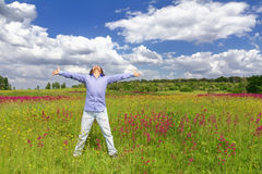 Man standing on a meadow on blue sky background Stock Photo
