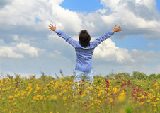 Man standing on a meadow with raised hands Stock Photo