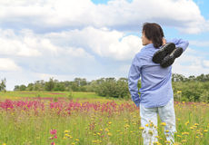 Man standing on a meadow with sneakers Royalty Free Stock Photo