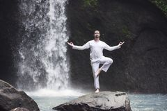 Man standing in meditation yoga on rock at waterfall Stock Image