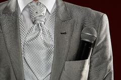 Man standing with microphone in  pocket. Man standing with microphone in pocket, isolated on dark background Royalty Free Stock Image