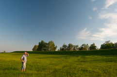Man standing in the middle of huge meadow Stock Image