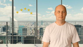 A man standing in a modern office with panoramic windows sets a rating on a virtual screen. Service rating 5 stars. Future technologies. City skyline outside stock video footage
