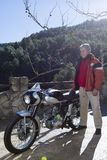 Man standing beside a motorbike Royalty Free Stock Photos