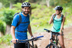 Man standing with mountain bike in forest Stock Photo