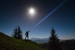 Man points by flashlight to the night sky. Man standing on a mountain hill and points by flashlight to the night starry sky Stock Photos
