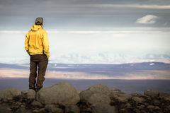 Man standing on mountain, looking relaxed towards snowy mountain range. Royalty Free Stock Images