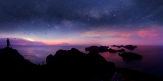 Man standing on the mountain with panorama view and million stars galaxy. Purple sky sunset at Ang thong archipelago island,Thailand royalty free stock photos