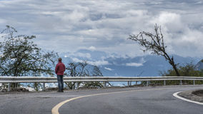 A man standing by the mountain road Stock Photos