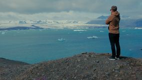 Man standing on mountain`s peak. Glacier lagoone. Man on mountain`s top. Ocean, icebergs and mountain in the background stock video footage